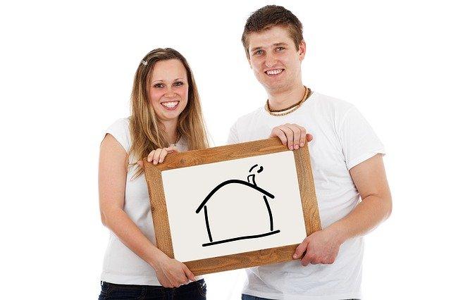 mladý pár držící obraz domu